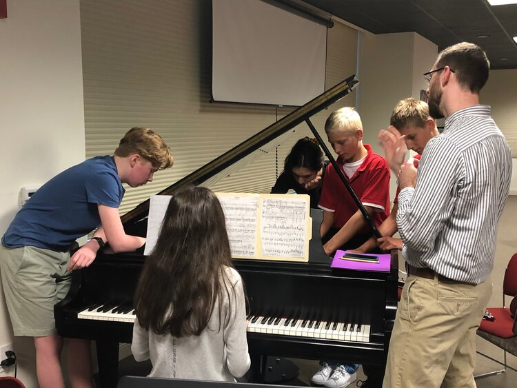 Kids in front of piano