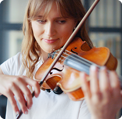 Romantic girl playing violin with bow looking at cords
